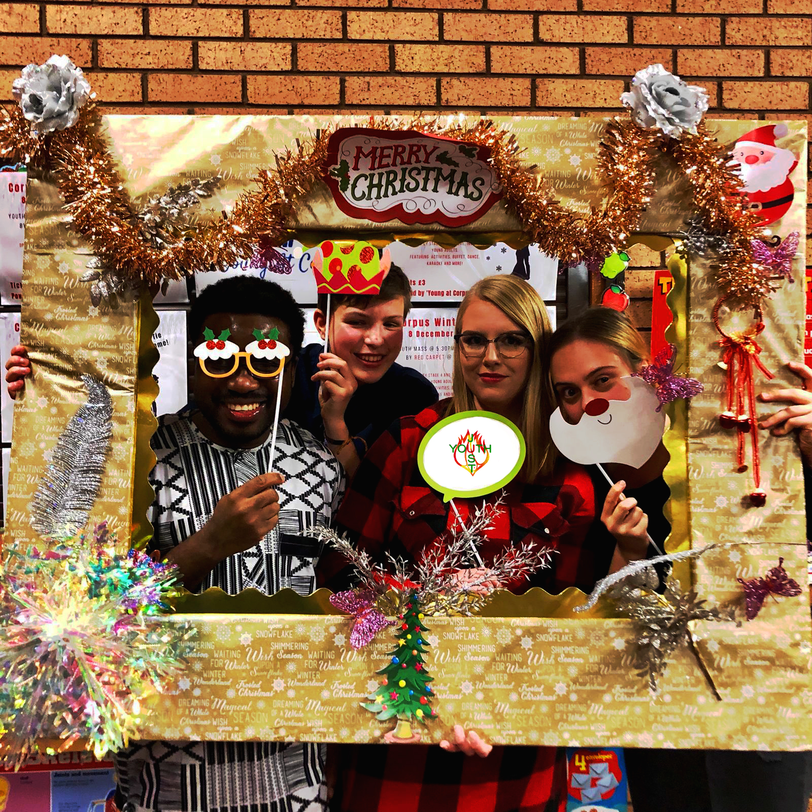 Image of Just Youth volunteers and Fr. David using funny props for a Christmas themed photobooth.